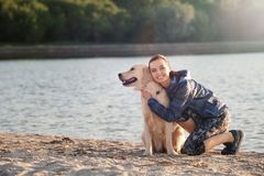 Young woman with her dog on beach. Pet care. Young woman with her dog together on beach. Pet care Royalty Free Stock Photos
