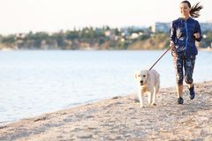 Young woman with her dog on beach. Pet care. Young woman with her dog together on beach. Pet care Royalty Free Stock Photography
