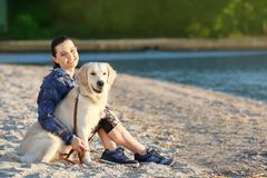 Young woman with her dog on beach. Pet care. Young woman with her dog together on beach. Pet care Royalty Free Stock Images