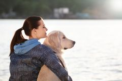 Young woman with her dog together near river. Pet care. Young woman with cute dog together near river. Pet care Stock Photography