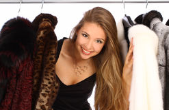 Young woman in her dressing room. Attractive young woman in her dressing room with a fur coats on the hanger Stock Photos