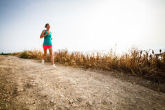Young woman on her evening jog along the seacoast. (motion blurred image Stock Photos