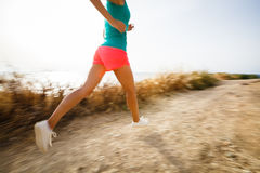 Young woman on her evening jog along the seacoast. (motion blurred image Stock Images
