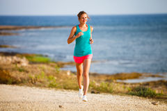Young woman on her evening jog along the seacoast Stock Images