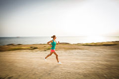 Young woman on her evening jog along the seacoast Royalty Free Stock Images