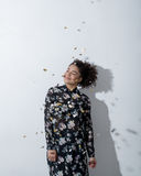 Young woman with her eyes closed. Standing near white wall and smiling under falling confetti Royalty Free Stock Images