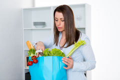Young woman with her food- shopping in the kitchen. Young dark haired woman with her food- shopping in the kitchen Royalty Free Stock Photo