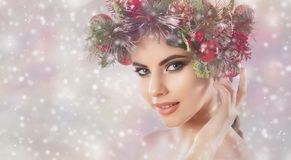 A young woman, on her head a beautiful wreath of spruce with cones and balls. royalty free stock image