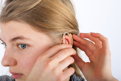 Young woman and her hearing aid. Close up of a deaf young womans ear when she inserting her hearing aid into ear royalty free stock photo