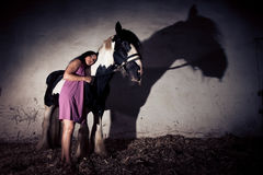 Young Woman With Her Horse. Young woman standing next to her horse in the stables Stock Photo