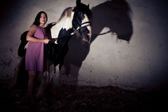 Young Woman With Her Horse. Young woman standing next to her horse in the stables Stock Images