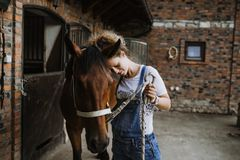Young woman with her horse. Young woman taking care of her horse royalty free stock images
