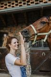 Young woman with her horse. Young woman taking care of her beautiful horse stock photos