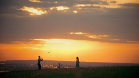 Young woman and her husband playing frisbee on the field, standing next to their little son, sunset summer evening - stock footage