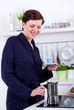 Woman in her kitchen preparing coffee with a moka pot Stock Images