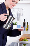 Woman in her kitchen preparing coffee with a moka pot Stock Image