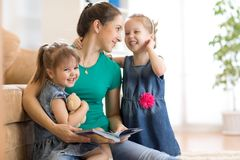 Young woman and her little children reading books at home. Young women and her little children reading books in living room at home stock photos