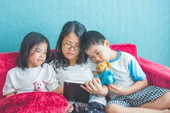 Young woman and her little children reading books on sofa at hom Stock Photos