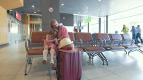 Young woman and her little daughter together have rest in the waiting room at the airport stock footage