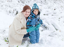 Young woman and her little son having fun with snow on winter da Stock Image
