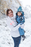 Young woman and her little son having fun with snow in winter fo Royalty Free Stock Photography