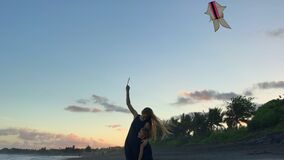 A young woman and her little son with a kite on a seashore. Shot on a phone
