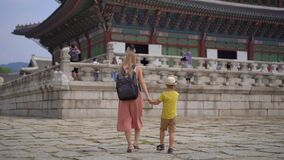 Young woman and her little son visit ancient palace in Seoul, South Korea. Travel to Korea concept. Slowmotion shot