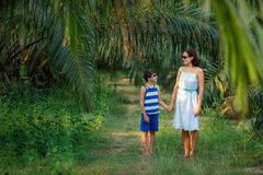 Young woman and her little son walking in tropical forest Royalty Free Stock Images