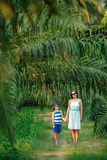 Young woman and her little son walking in tropical forest Stock Photography