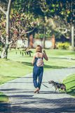 Young woman with her lovely beagle dog in the park of Bali island, Indonesia. Royalty Free Stock Photography