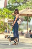 Young woman with her lovely beagle dog in the park of Bali island, Indonesia. Young woman with her lovely beagle dog in the park of Bali island Royalty Free Stock Image