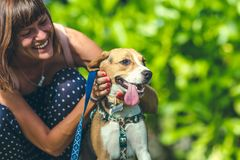 Young woman with her lovely beagle dog in the park of Bali island, Indonesia. Royalty Free Stock Image