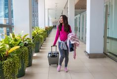 Young woman with her luggage at an international airport. royalty free stock images