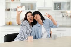 Young woman and her mature mother taking selfie at table royalty free stock photos