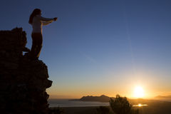 Young woman during her morning pray. Looking to the beautiful landscape Stock Image