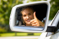 Young woman in her new car with thumb up Stock Images