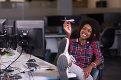 Young woman at her office workplace playing with plane toy Royalty Free Stock Images