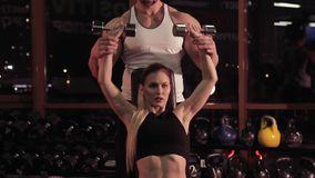 Young woman and her personal fitness trainer in the gym with dumbbells