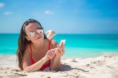 Young woman with her phone on exotic beach Royalty Free Stock Image