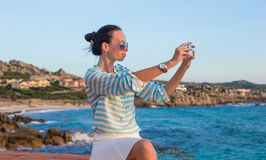 Young woman with her phone during summer vacation Stock Photography