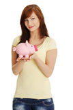 Young woman with her piggy bank Royalty Free Stock Image