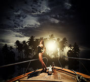 Young woman on her private yacht. Young sexy woman on her private yacht at sunset around tropical island Stock Photo