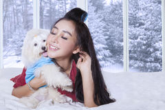 Young woman and her puppy lying on bed. Image of a young happy woman lying on the bedroom while hugging her puppy, shot at home with winter background on the Stock Images