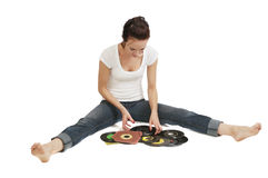 Young Woman And Her Record Collection. Pretty young woman looking through her 45 rpm records for one to play Royalty Free Stock Photography