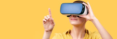 Young woman in her 30s using virtual reality goggles. Woman wearing VR headset isolated over yellow banner. VR experience. stock photos