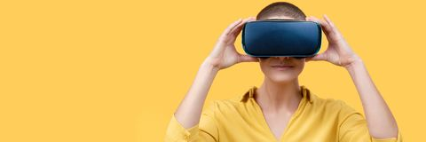 Young woman in her 30s using virtual reality goggles. Woman wearing VR headset isolated over yellow banner. VR experience. stock photography