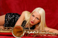 Young woman with her Saxophones. Young handsome musician behind her Saxophones Royalty Free Stock Photography