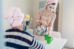 Young woman with her senior mother preparing tea with facial masks applied. Women chilling and talking on kitchen royalty free stock photography