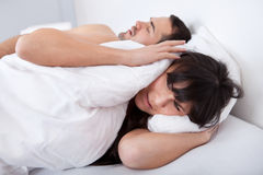 Young woman and her snoring boyfriend Royalty Free Stock Images