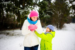 The young woman and her son cheerfully play in the winter park. Royalty Free Stock Images